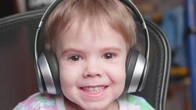 Ein kleiner lustiger Junge sitzt in einem Stuhl und hört Musik durch Kopfhörer Nahes hohes des Gesichtes Lizenzfreies Stockfoto