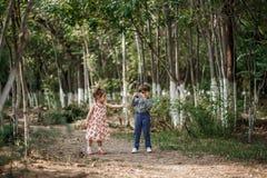Ein kleiner netter Junge in der Weinlesekleidung und ein kleines schönes Mädchen in einem Retro- Kleid gehen im Wald und machen F lizenzfreie stockfotos