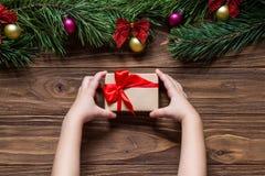 Ein kleiner netter Kasten in den Kind-` s Händen Nettes Weihnachtsthema mit Geschenk und Lametta auf dem hölzernen Hintergrund Stockbild