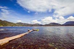 Ein kleiner Pier für Boote auf einem klaren Wasser auf einem Hintergrund die Berge Stockfotos