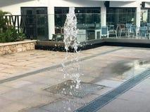 Ein kleiner schöner Gesangbrunnen im Freien, auf der Straße Wassertropfen, Wasserstrahlen im Flug eingefroren in der Luft wieder Lizenzfreie Stockbilder
