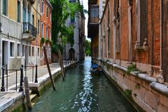Ein kleiner schmaler Kanal in Venedig, Gondel, Backsteinhäuser stockfotografie