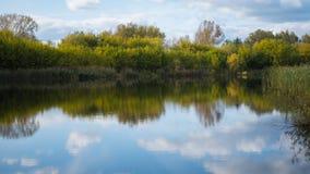 Ein kleiner See im Park, die gelb färbenden Bäume entlang dem Ufer Die Reflexion des Himmels und der Bäume im Wasser des Sees Lizenzfreie Stockbilder