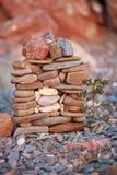Ein kleiner Steinhausbau mit einem Baum vor ihm auf Strandhintergrund Lizenzfreie Stockfotos