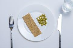 Ein kleiner Teil Nahrung auf einer großen Platte auf einer weißen Tabellennahaufnahme lizenzfreie stockfotografie