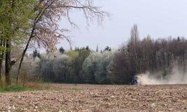 Ein kleiner Traktor kultiviert ein gepflogenes Feld im Wald lizenzfreie stockfotos