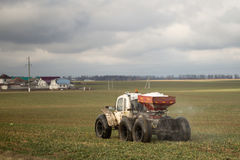 Ein kleiner Traktor läuft in das Feld im Vorfrühling Stockfotografie