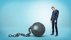 Ein kleiner trauriger Geschäftsmann, der unten zu einem riesigen Eisenklotz am bein auf blauem Hintergrund schaut lizenzfreie stockbilder