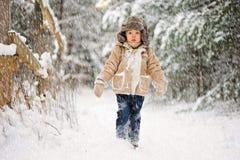 Ein kleiner trauriger Junge in schneiendem Winter lizenzfreie stockfotos