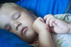 Ein kleiner unverschämter Junge schläft süß auf einem weichen Lehnsessel nach dem Abendessen lizenzfreie stockfotografie