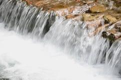 Ein kleiner Wasserfall Der Höhenunterschied des Wasserstroms im Fluss wird mit runden hölzernen Klotz ausgerüstet stockfotografie