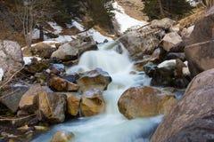 Ein kleiner Wasserfall zwischen großen Steinen Stockfotos