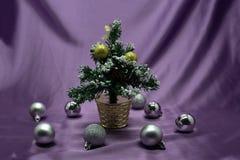 Ein kleiner Weihnachtsbaum in einem Topf, verziert mit Bällen, Girlanden und Lichtern Stockbild