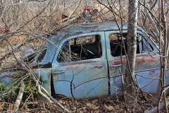 Ein kleines altes blaues Auto verlassen im Wald während der Seitenansicht der Wintermonate lizenzfreie stockbilder