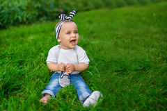 Ein kleines Baby in einem Denim kleidet sitzt auf einem Gras lizenzfreies stockbild