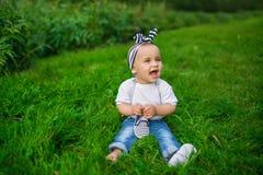 Ein kleines Baby in einem Denim kleidet sitzt auf einem Gras stockbild