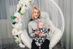 ein kleines Baby mit Mutter auf ihren Händen auf einem runden Schwingen lächelt stockfotos