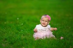 Ein kleines Baby in rosa Kleidung sitzt auf einem Gras stockfotografie
