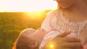 Ein kleines Baby schläft in den Armen seiner Mutter, bei Sonnenuntergang, Zeitlupeschießen stockfotografie