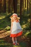 Ein kleines blondes Mädchen in einem hellen Kleid und in einem Hut geht in eine Kiefer f Stockbild