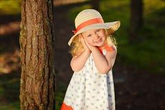 Ein kleines blondes Mädchen in einem hellen Kleid und in einem Hut geht in eine Kiefer f Lizenzfreie Stockfotografie