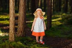Ein kleines blondes Mädchen in einem hellen Kleid und in einem Hut geht in eine Kiefer f Lizenzfreies Stockbild