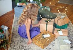 Ein kleines blondes Mädchen im bunten Kleid sitzt im Raum mit Kamin auf backround Geschenken Glücklicher Mann genießt an den Feie lizenzfreies stockbild