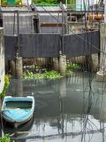 Ein kleines Boot, das in verschmutztes Wasser in Bangkok schwimmt lizenzfreie stockfotos