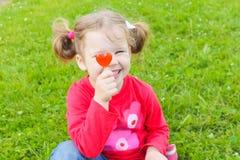 Ein kleines, boshaftes Mädchen, das eine Süßigkeit auf einem Stock hält Hübscher Gi Lizenzfreies Stockbild