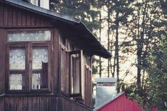Ein kleines Fenster in der Wand eines alten Holzhauses Stockfotografie