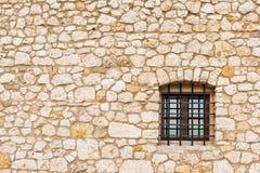 Ein kleines Fenster eines Kerkers mit einem Gitter und der Steinwand mit stockbilder