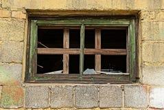 Ein kleines Fenster mit defekten Glasplatten auf einer Backsteinmauer Stockbilder