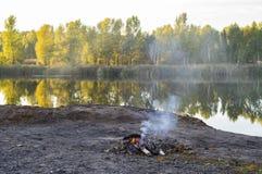 Ein kleines Feuer brennt auf dem Ufer stockbild