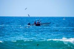 Ein kleines Fischerboot wurde mit vielen Seemöwen gesehen, die nah an es fliegen lizenzfreie stockfotos