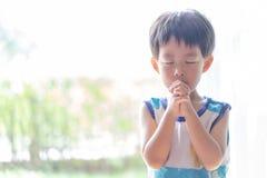 Ein kleines Gebet, ein Junge betet ernsthaft und hoffnungsvoll zu Jesus stockbilder