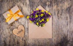 Ein kleines Geschenk mit einem Goldband, ein Umschlag mit Blumen und ein Herz Romantisches Konzept Lizenzfreies Stockfoto