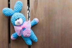 Ein kleines gestricktes blaues Kaninchen mit rosa bowtie auf einem alten hölzernen Hintergrund Gestricktes Spielzeug, handgemacht Stockbild