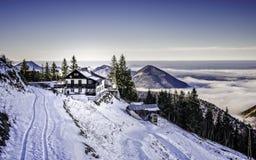 Ein kleines Haus auf einem schneebedeckten Bergabhang nahe bei schmaler Straße Lizenzfreies Stockfoto