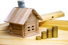 Ein kleines Haus, das an den Baumaterialien und den Münzen steht Kredit f Stockfotografie