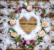 Ein kleines Herz ausgebreitet vom Schnee auf einem Holztisch stockbild
