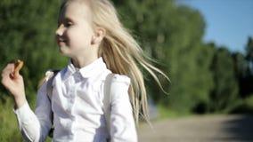 Ein kleines hungriges blondes Schulmädchen läuft zur Schule auf der sandigen Straße das Feld durch und isst einen Keks stock video