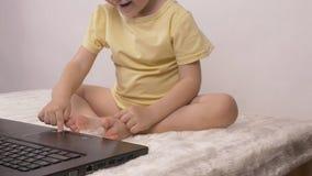 Ein kleines Kind bedrängt einen Finger auf dem Knopf auf der Laptoptastatur, -nahaufnahme, -baby und -computer lizenzfreies stockfoto
