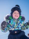 Ein kleines Kind, das im Winter Park spielt Spielendes und l?chelndes Baby auf blauem Hintergrund Aktiver Rest und Spiele lizenzfreie stockfotos