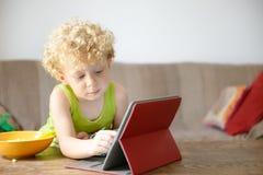 Ein kleines Kind, das mit einer Tablette spielt Lizenzfreie Stockfotos