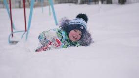 Ein kleines Kind, das mit Schnee in Winter Park spielt Lügenund lächelndes Baby auf weißem flaumigem Schnee Spaß und Spiele im fr Stockfotografie