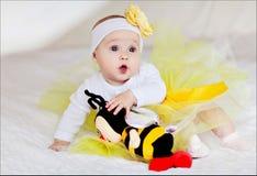 Ein kleines Kind in einem gelben Rock sitzt auf dem Bett mit einer Spielzeugbiene lizenzfreies stockbild