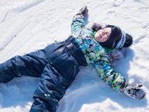 Ein kleines Kind geht in den Winter Park Spielendes und lächelndes Baby auf weißem flaumigem Schnee Aktiver Rest und Spiele stockfotos