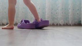Ein kleines Kind geht in erwachsene große Turnschuhe um das Haus, erwachsene Pantoffel auf Kind-` s Füßen, Haus stock video footage