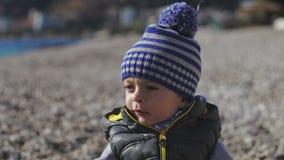 Ein kleines Kind lächelt in die Kamera und in die Spiele auf dem Strand mit Kieseln stock video