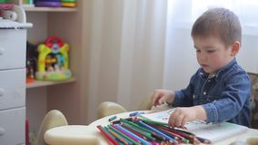 Ein kleines Kind lernt, mit farbigen Bleistiften auf Papier zu zeichnen stock footage